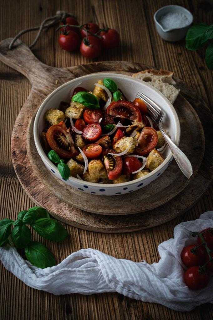 Ein Teller Bruschetta Salat aus Tomaten und geröstetem Brot auf einem Holzbrettchen
