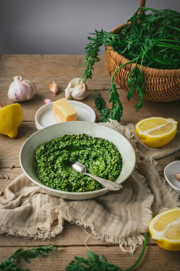 Das Pesto steht auf einem Tisch. Daneben liegen die Zutaten des Pestos, wie Zitronen, Knoblauch und Karottengrün.