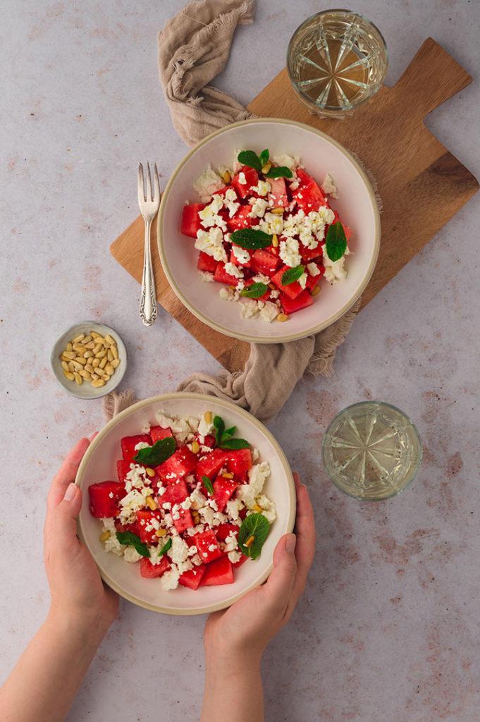 Eine Person nimmt sich eine Schale mit Wassermelonen Feta Salat vom Tisch.