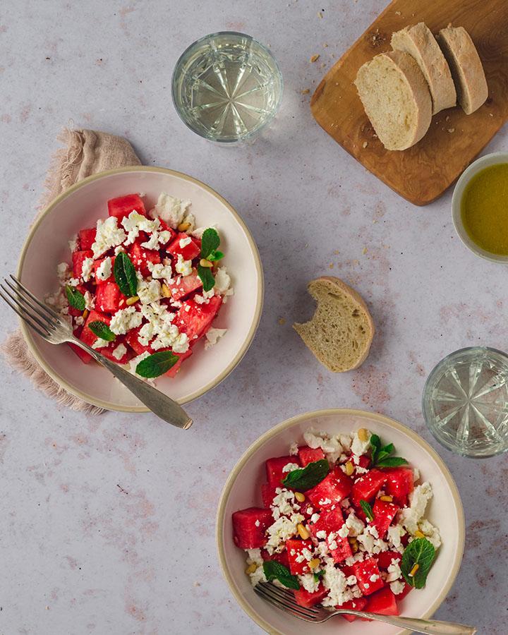 Der Melonensalat mit Brot und Weißwein auf einem Tisch angerichtet