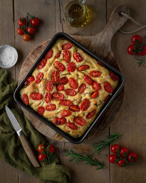 Die Focaccia mit Tomaten steht frisch aus dem Ofen auf dem Tisch.