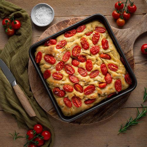 Die vegane Focaccia mit Tomaten ist frisch aus dem Ofen geholt und steht auf einem Tisch zum Abkühlen.