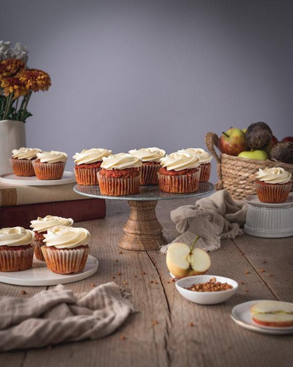 Muffins aus Entsafterresten stehen auf einem Holztisch mit Buttercreme verziert.