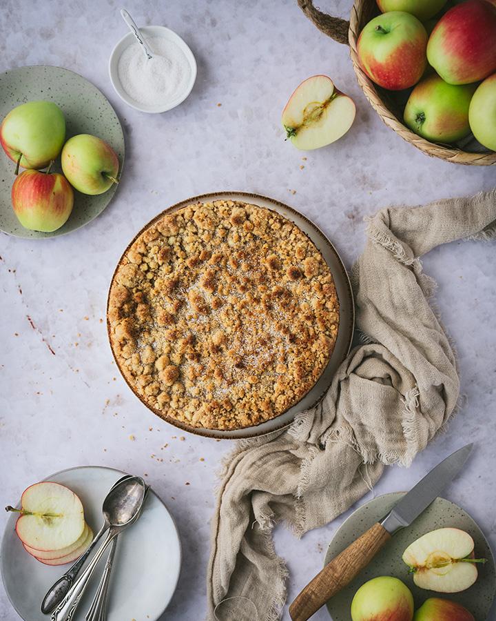 Der Kuchen steht auf dem Tisch. Daneben Teller und Besteck, damit er angeschnitten und serviert werden kann.