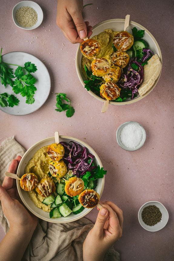 Zwei Personen essen selbstgemachte Falafel aus Kichererbsenmehl an einem Tisch.