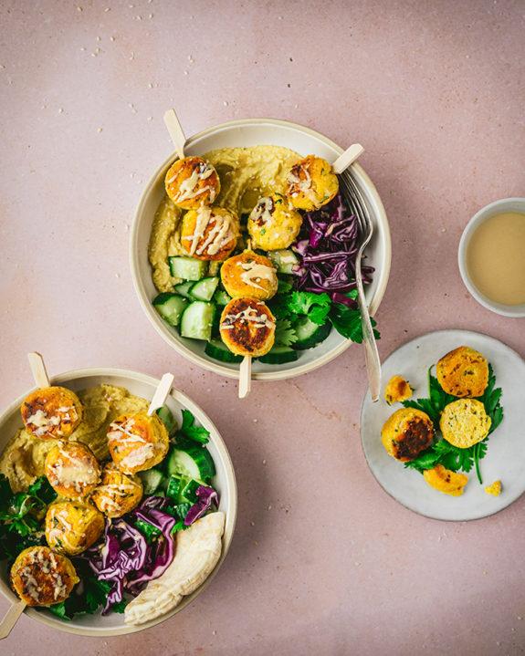 Drei Teller mit selbstgemachte Falafeln, Humus und Krautsalat stehen auf einem Tisch.