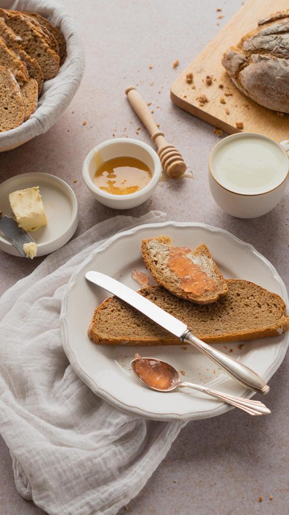 Brot mit einer Tasse Milch, Honig und Marmelade
