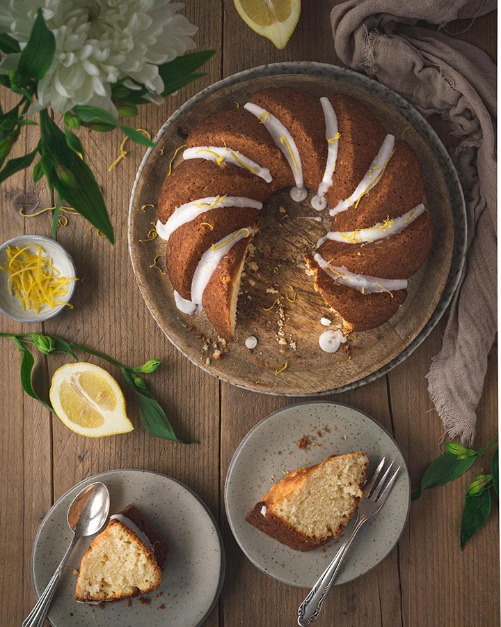 Ein Gugelhupf auf einem Tisch. Daneben liegen zwei Stücke des Kuchens auf einem Teller.