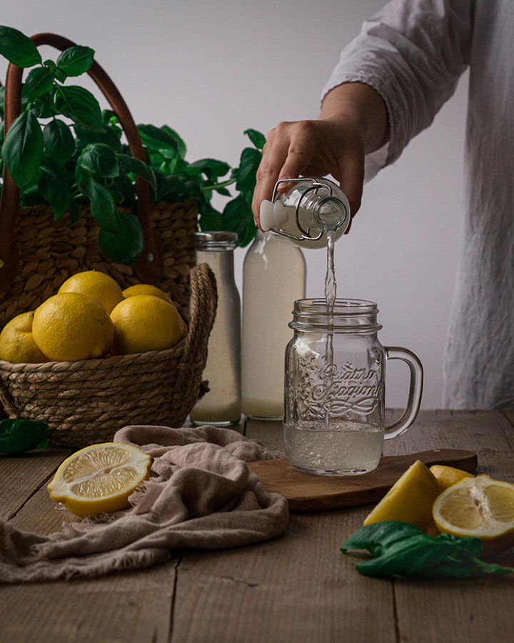 Eine Frau gießt Basilikum Zitronen Sirup in ein Glas