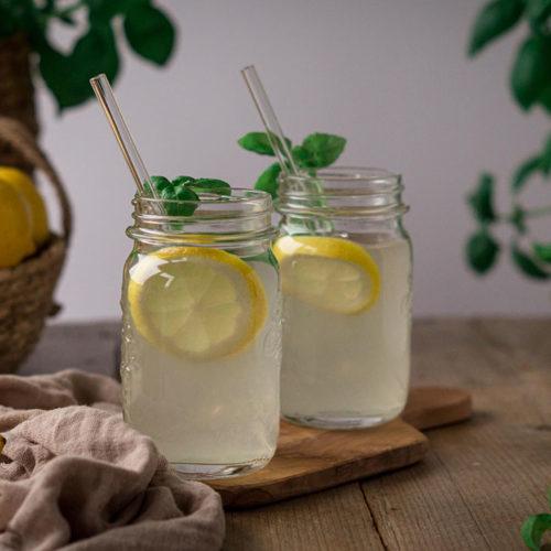 Basilikum-Zitronen-Limonade in Gläsern mit Glas-Strohhalmen auf einem Tisch