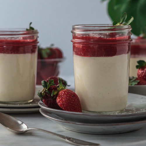 Panna Cotta mit Erdbeersauce in kleinen Gläsern auf einem Tisch