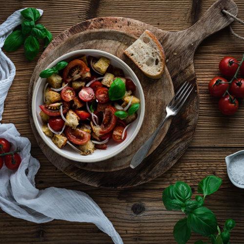 Ein Teller mit Panzanella aus altem Brot und Tomaten auf einem Tisch