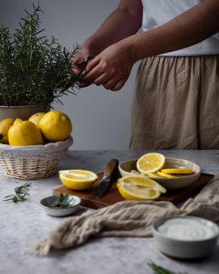 Eine Frau schneidet Rosmarin von Zweigen ab. Im Vordergrund stehen Zitronen.