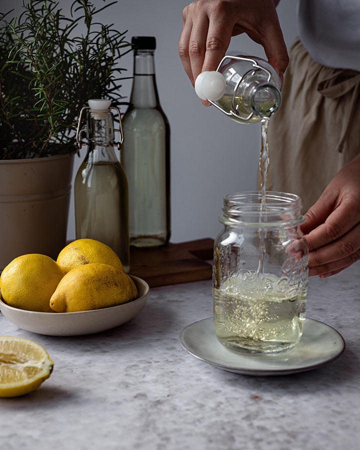 Eine Frau gießt Sirup in ein Glas.