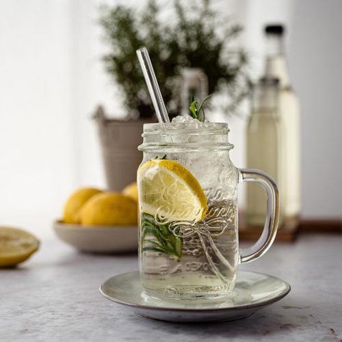 Eine großes Glas Rosmarin Zitronen Limonade auf einem Tisch.