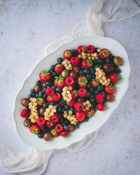 Viele unterschiedliche Beeren auf einer Servierplatte drapiert, um Beeren richtig aufzubewahren