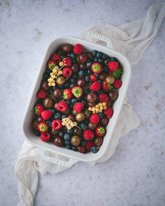 Eine Schüssel voller Beeren auf einem weißen Untergrund