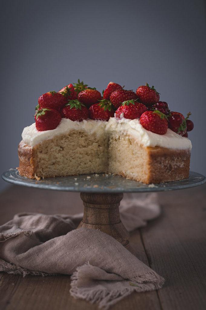 Der Kuchen ist angeschnitten und steht auf einem Tisch. Man sieht den fluffigen Teig von innen.