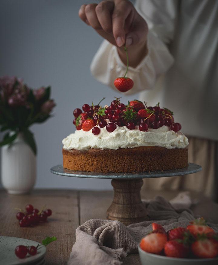 Eine Frau legt die letzte Erdbeere auf den veganen Biskuitboden mit Beeren