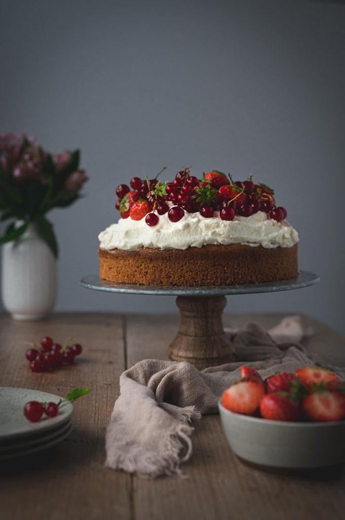 Der Kuchen steht fertig dekoriert auf einen Tisch. Daneben liegen Teller bereit.