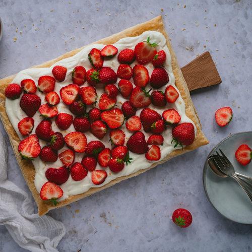 Eine Blätterteig Tarte mit Beeren liegt auf einem Holzbrettchen. Daneben stehen Teller und Besteck bereit.