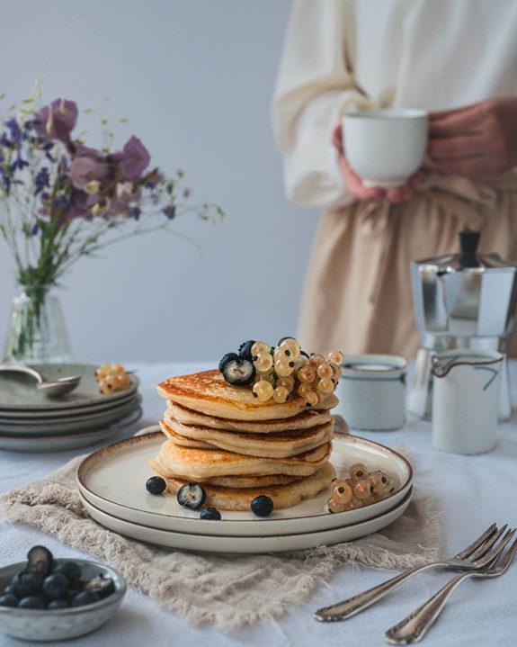 Im Vordergrund steht ein Teller mit Panckes auf dem Tisch. Eine Frau steht im Hintergrund und trinkt eine Tasse Kaffee.