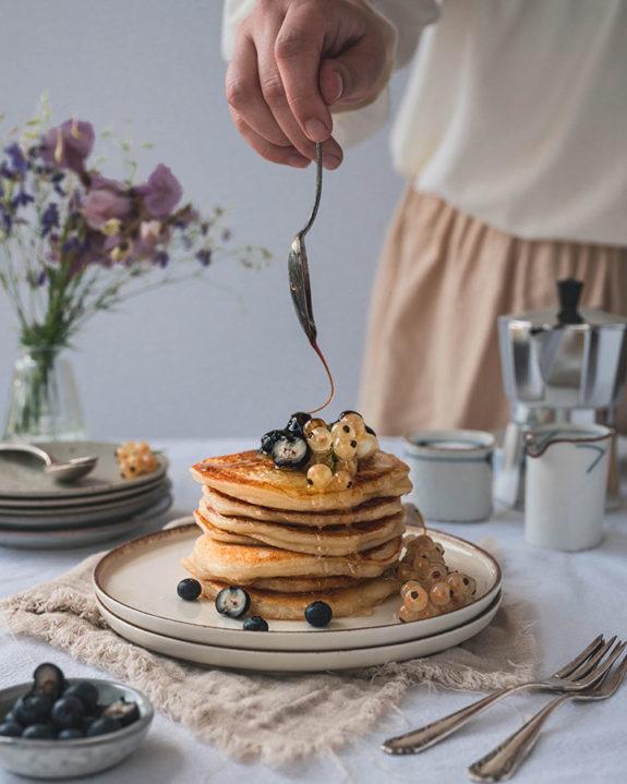 Eine Frau gießt Sirup auf einen Stapel Pancakes.