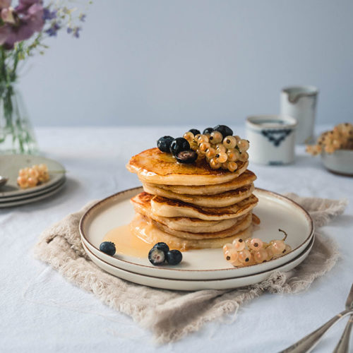 Ein Teller mit aufeinander gestapelten Ricotta Pancakes ohne Ei, die mit Beeren dekoriert sind.