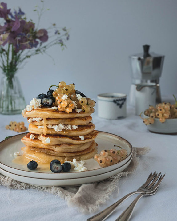 Ein Teller mit Pancakes steht auf einem Frühstückstisch. Die Panckes sind mit Ricotta und Beeren garniert.