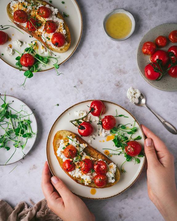 Eine Frau nimmt sich einen Teller mit Ricotta Toast vom Tisch.