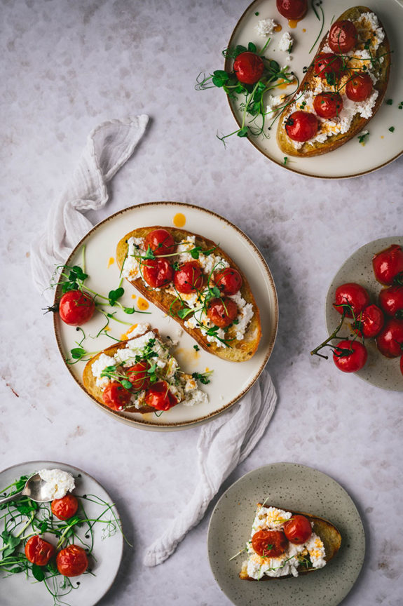Drei Teller mit Ricotta Toast mit karamellisierten Tomaten auf einem Tisch.