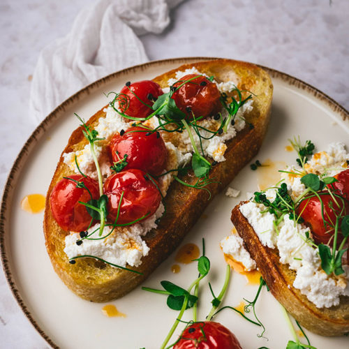 1,5 Scheiben Ricotta Toast mit karamellisierten Tomaten auf einem Teller.