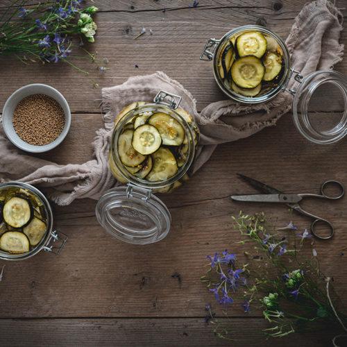 Drei Weckgläser mit eingelegten Zucchini auf einem Tisch
