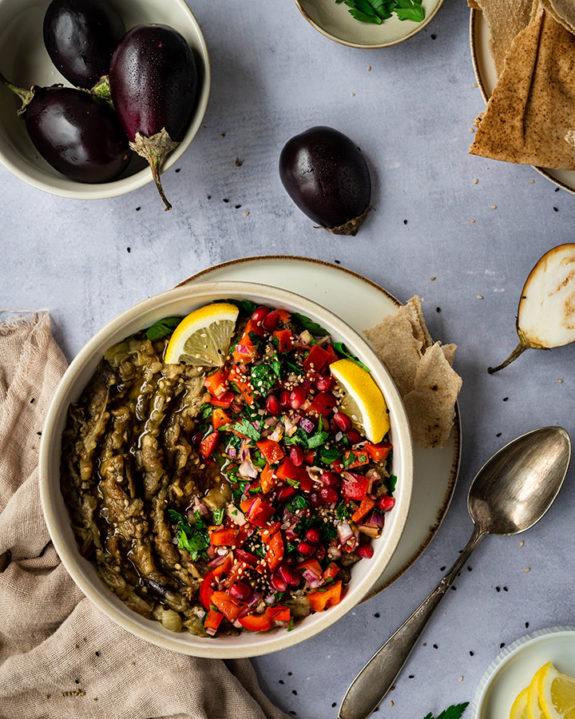 Eine Schale mit Baba Ganoush steht auf einem Tisch. Daneben liegen die Zutaten für den Auberginensalat.