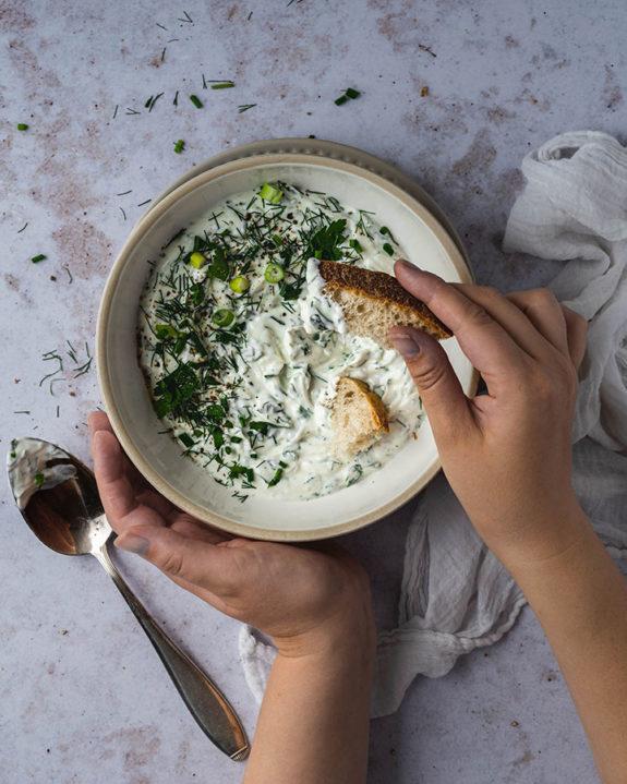 Eine Frau dippt mit einem Stück Brot in die Schüssel mit dem selbstgemachten Kräuterquark.