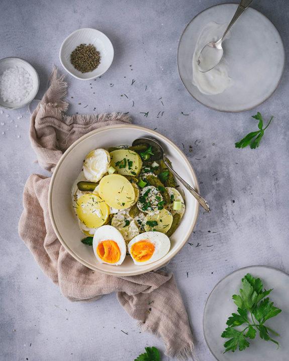 Eine Schüssel mit Kartoffel-Eier-Salat steht auf einem Tisch. Daneben stehen Teller, bereit zum Servieren.