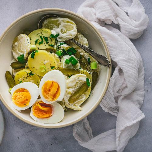 Eine große Schüssel Kartoffelsalat mit Eiern steht auf einem Tisch.