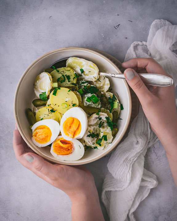 Eine Frau hält eine Schüssel mit Kartoffel-Eier-Salat in ihrer Hand und greift nach einem Löffel.