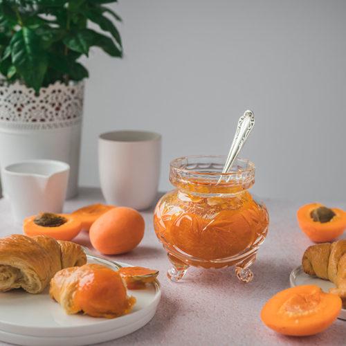 Ein Glas mit Aprikosenmarmelade steht auf einem Tisch.