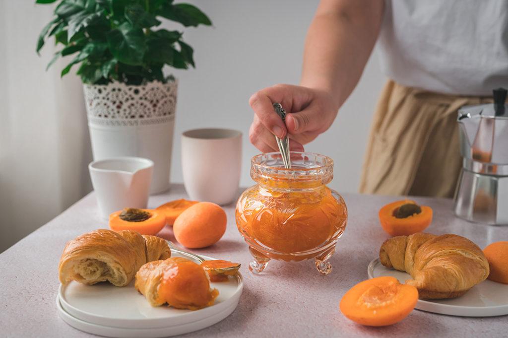 Eine Frau dippt ein Croissant in Aprikosen-Marmelade