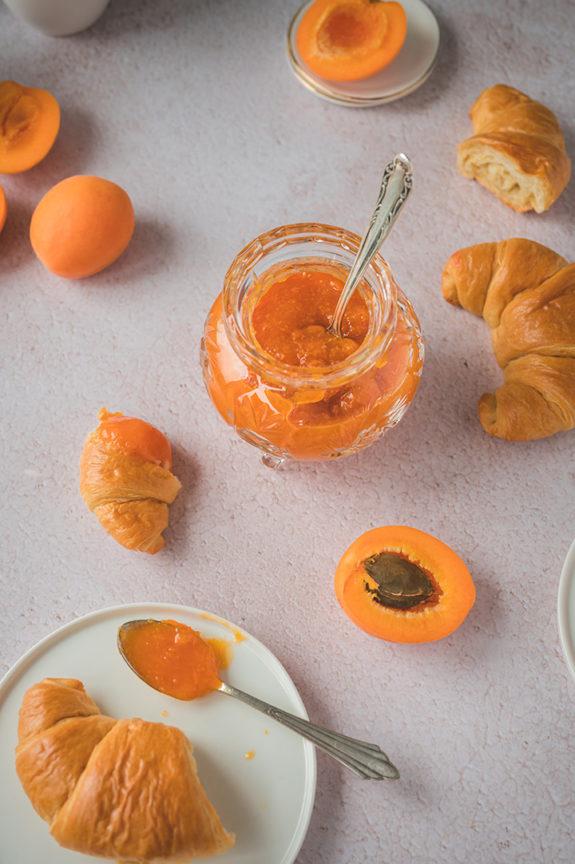 Ein geöffnetes Glas mit selbstgemachter Aprikosenmarmelade steht auf einem Tisch.