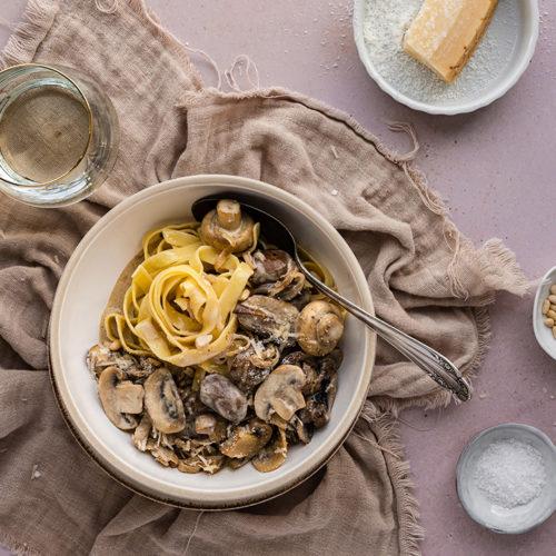 Ein Teller voll Pasta mit Champignon-Rahmsauce steht auf einem Tisch.