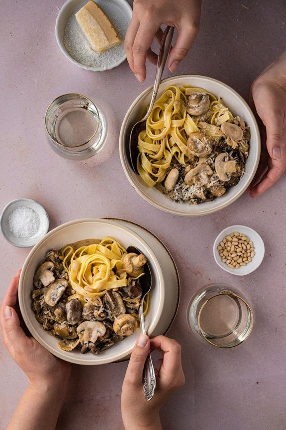 Zwei Personen sitzen sich gegenüber und essen Pasta mit Champignon-Rahmsauce.