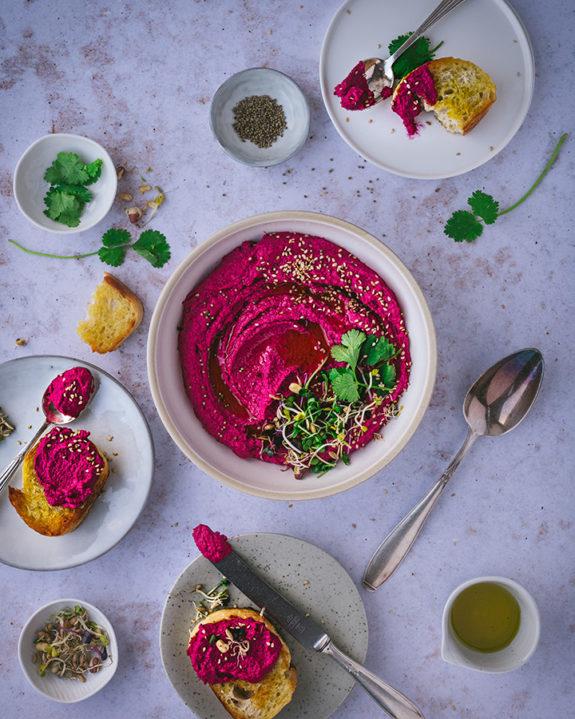 Eine Schüssel mit Rote Bete Humus steht auf einem Tisch. Daneben sind kleine Teller mit Brot zu Dippen.