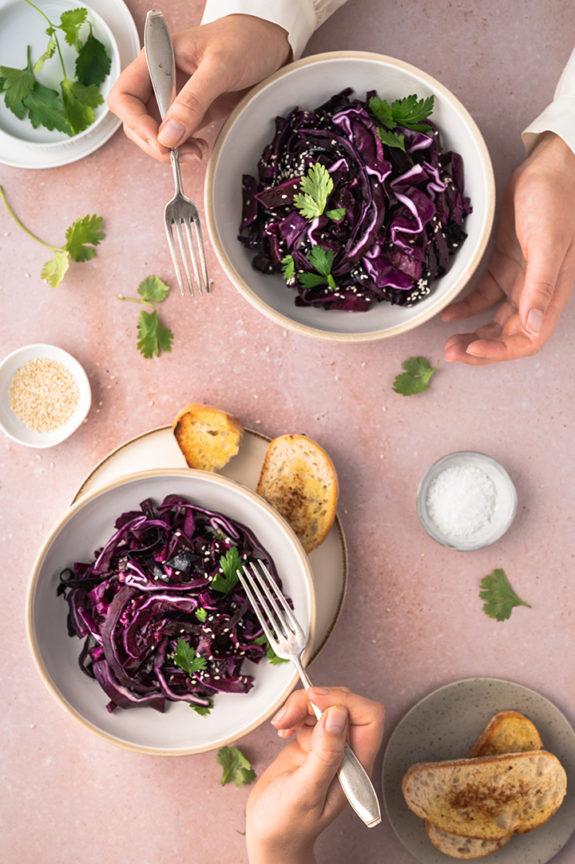 Zwei Personen essen jeweils eine Schüssel mit schnellen Rotkohlsalat an einem Tisch
