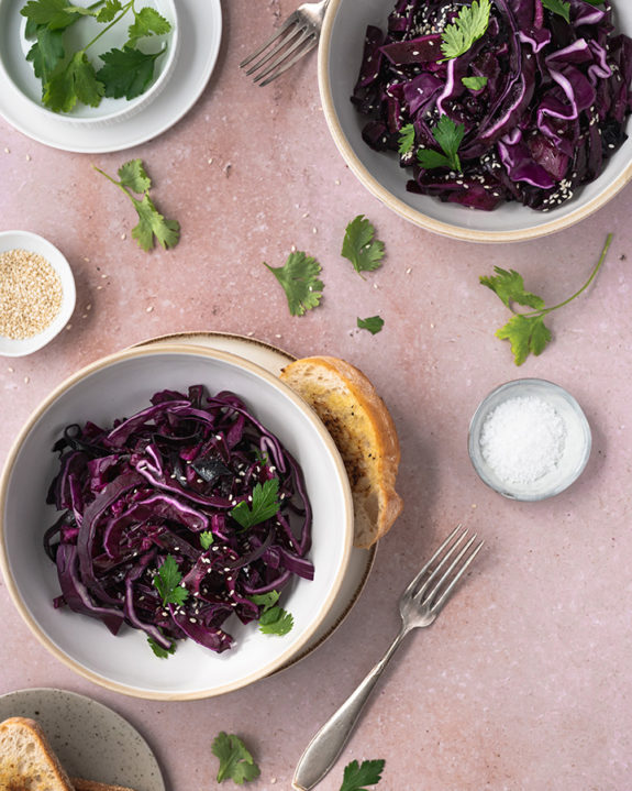 Zwei Schüsseln mit schnellem Rotkohlsalat stehen auf einem Tisch.