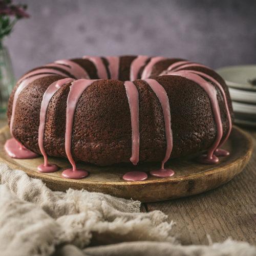 Ein veganer Rotweinkuchen als Gugelhupf steht auf einem Tisch.